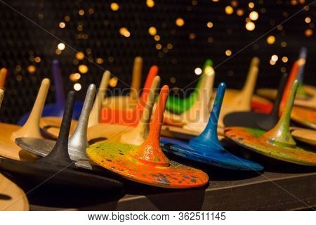 Front View On Colorful Handmade Painted Wooden Toys - Peg Tops Or Whirligigs As Creative Background