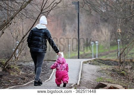 Mom And Kid Are Walking Down The Path Holding Hands. Young Slender Woman Lead Little Girl In A Sprin