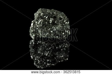A Cluster Of Pyrite Crystals. Isolated On A Black Mirror Background.