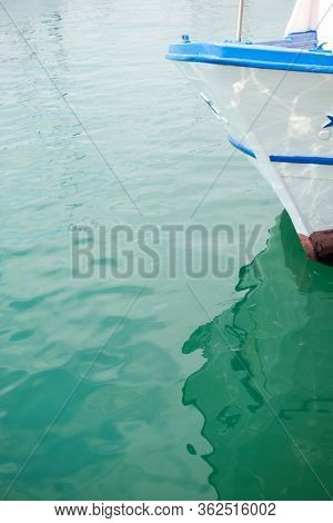 Ship's bow and aquamarine water in the port of Syracuse, Sicily. Boat and sea, detail. Sailing vessel drops anchor in a quiet bay