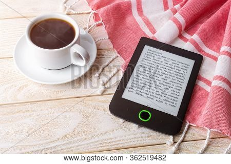 Cup Of Hot Coffee Near E-book Reader Over Red Cotton Stole On A White Wooden Surface. E-reading For