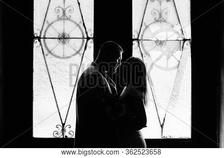 Portrait Of A Romantic Couple In A Backlight From A Window Or Door, Silhouette Of A Couple In A Door