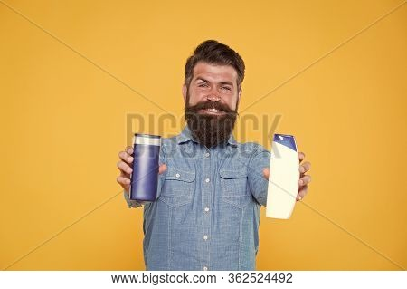 Essential For Good Hygiene. Hipster Hold Gel And Shampoo Bottles. Bearded Man With Hygiene Products.