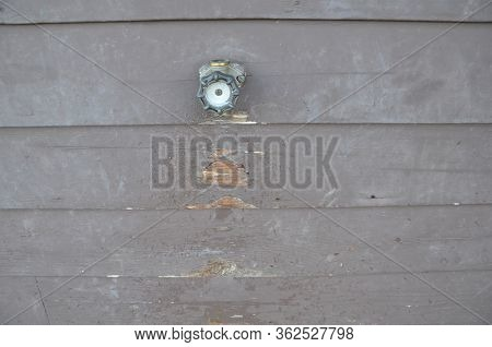 Damaged Brown Wood Wall With Hose Spigot