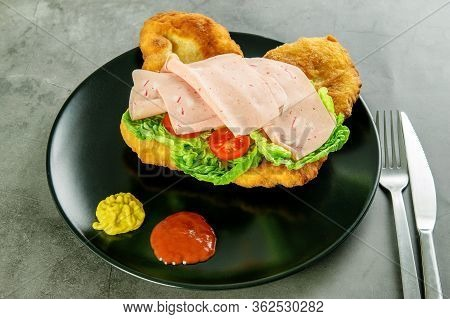 Navajo Bread, Taco With Tomotoes, Green Lettuce, Ham And Sauce On The Black Plate, Cutlery On The Da