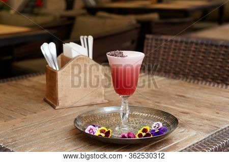 Red cocktail with froth and chocolate on pub table, decorated with violet flowers
