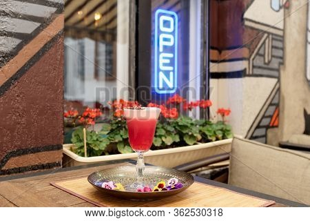 Red cocktail with froth and chocolate on pub table