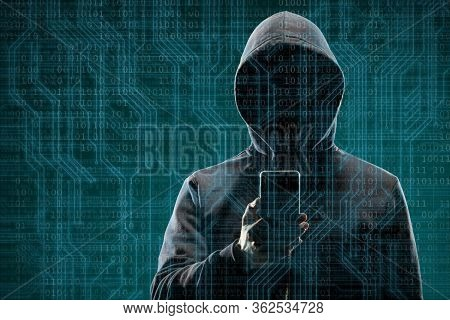 Anonymous Computer Hacker With A Smartphone Over Abstract Digital Background. Obscured Dark Face In