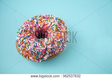 Donut with pink icing and candies on a blue pastel background