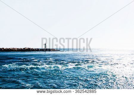 Ocean Current Landscape Background. Small Lighthouse By The Shore. Empty Copy Space White Sky And Bl