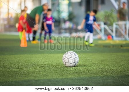 Old Soccer Ball On Green Artificial Turf With Blurry Soccer Team Training.