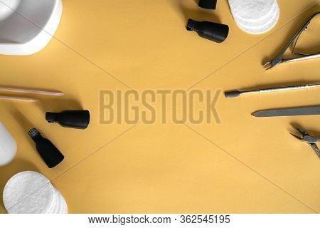 Manicure Tools On A Pastel Yellow Background. Tongs, Nail File, Pusher, Cotton Pads. Home Manicure.
