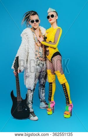 A full length portrait of two cool young punk people posing in the studio. Modern punk fashion, rock band.