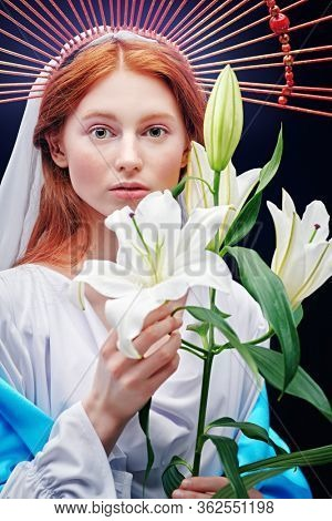 The Virgin Mary portrait with lilies on a dark background with rays of light. Modern art in religion.