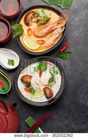 Tom Yum and Tom Kha traditional Thai soups with seafood, chicken, mushrooms, coconut milk and hot spices. With green tea pot and bowl. Top view