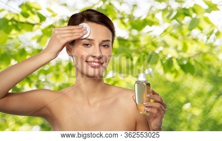 beauty, skin care and people concept - smiling young woman with toner or cleanser and cotton pad cleansing face over green natural background