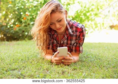 Closeup Portrait Smiling Young Woman Touching Cell Texting By Phone And Lying On Meadow Grass Outsid