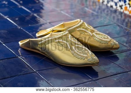 Traditional Moroccan pair of festive golden slippers at a floor with blue tiles