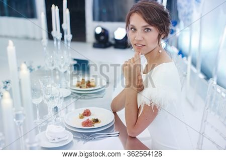 Beautiful Young Bride With Wedding Makeup And Hairstyle In The Banquet Hall With A Chic Wedding Desi