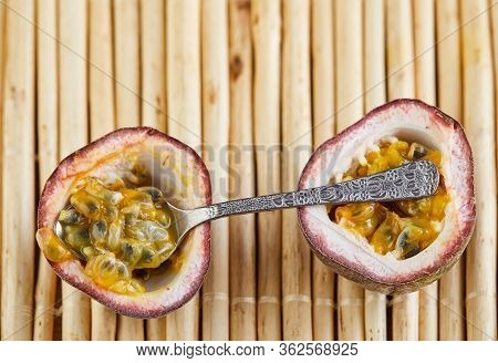 Passiflora Is Cut Into Two Halves With A Spoon Inside On A Bamboo Background. Flat Lay.
