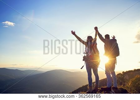Happy Couple Man And Woman Tourist At Top Of Mountain At Sunset Outdoors During A Hike In Summer