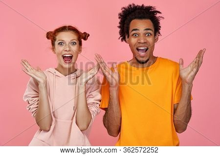 Happy Joyful Young Ginger Woman And African Man Exclaim Loudly, Being In High Spirit, Keep Mouth Ope