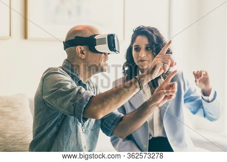 Excited Mature Man Testing Virtual Reality Headset. Caucasian Man Experiencing Vr Headset With Assis