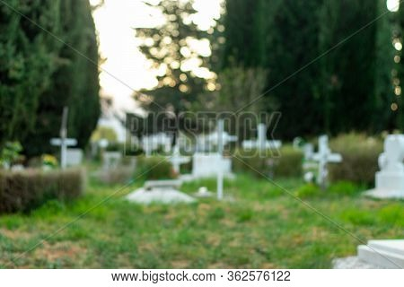 Out Of Focus Image Of A Graveyard. Green Bright Grass, Outlines Of Multiple White Crosses Recognisab