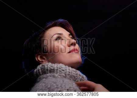 Portrait Of A Beautiful, Charming Young Woman In In A Grey Thick Knitted Sweater And A Black Backgro