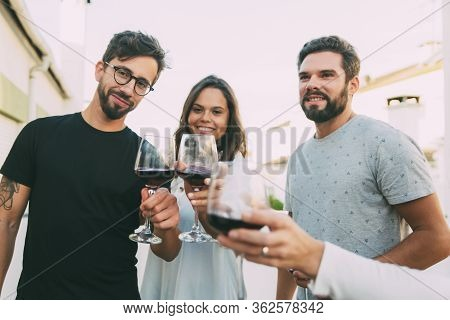 Cheerful Friends Toasting To Camera With Glasses Of Red Wine. Cheerful Friends Posing With Red Wine