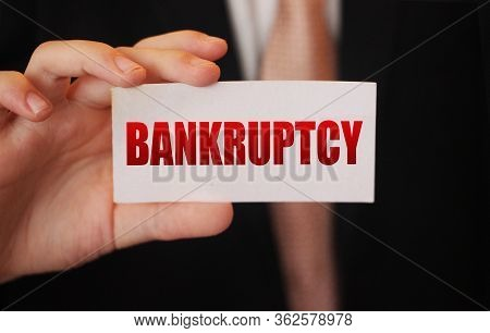 Bankruptcy On A Card. Businessman Holding A Card With Word Bankruptcy. Crisis Business Closing Debts