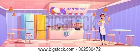 Saleswoman In Ice Cream Shop Or Parlor. Girl Seller Holding Icecream Cone Stand Near Table With Chai