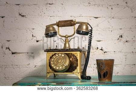 Retro Composition Of Golden Antique Telephone Set And Pottery Mug On Green Vintage Wooden Table And