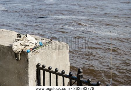 Fishing Rod On The Background Of River Water And A Backpack With Fishing Tackle On A Concrete Parape