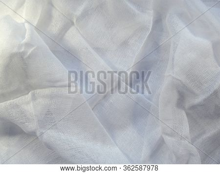 Medical Gauze Lies Carelessly With Folds On A White Surface. Clean Blank White Mesh Fabric Pattern