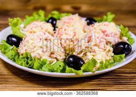 White Plate With Crab-cheese Balls, Black Olives And Lettuce Leaves On Rustic Wooden Table