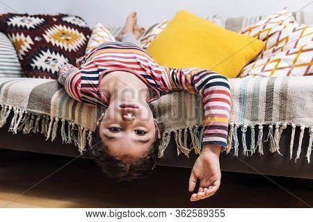 Little Girl Gets Bored Lying On The Couch, Concept Of Children At Home And Home Lifestyle