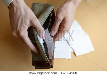 Empty Wallet With Paper Instead Of Money In The Hands Of A Man On A Light Monophonic Background, Top