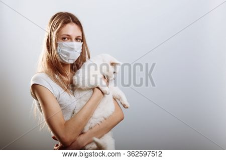 Yound Lady In Protective Surgical Mask Holds Cat Pet. Coronavirus Disease Covid-19 Is Dangerous For