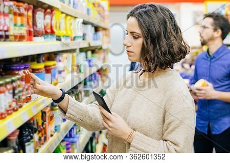 Woman Holding Smartphone And Choosing Goods In Supermarket. Young Woman Reading Checklist Via Smartp