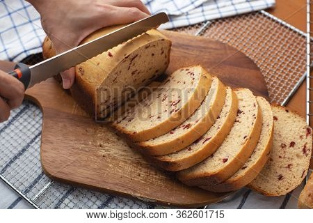 Homemade Cranberry Bread With Woman Hand Slicing On Wooden Cutting Board
