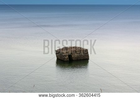 Old German Bunker Is Rinsed Out In The Sea On The Cliffs Of The Baltic Coast