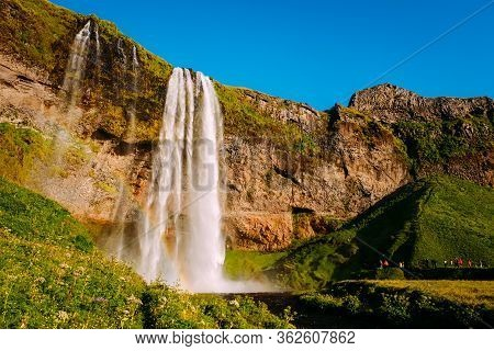 Big Seljalandsfoss Waterfall In Iceland At Summer Sunset And Small Figures Of Tourists Next To It