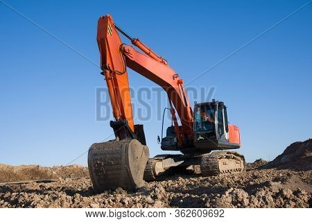 Excavator During Earthmoving Work At Open-pit Mining On Blue Sky Background. Loader Machine With Buc