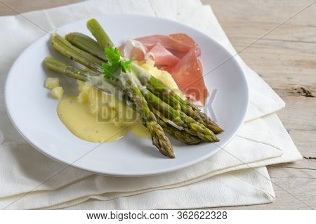 Green Asparagus Served With Mashed Potatoes, Ham And A Light Hollandaise Sauce On A White Plate On A