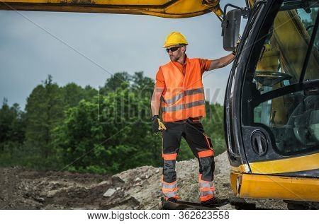Excavator Operator Looks At Construction Site Standing On Heavy Duty Earthmoving Equipment.