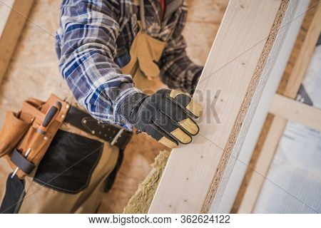 Construction Contractor Insulates Newly Built Walls In House.