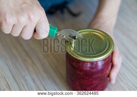 A Woman In The Kitchen Opens A Can Of Canned Borscht With A Hand-held Can Opener