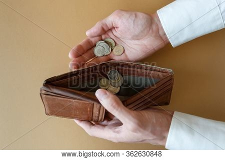 Empty Wallet In The Hands Of A Man On A Light Solid Background, Top View. Coins In Hand And In An Em