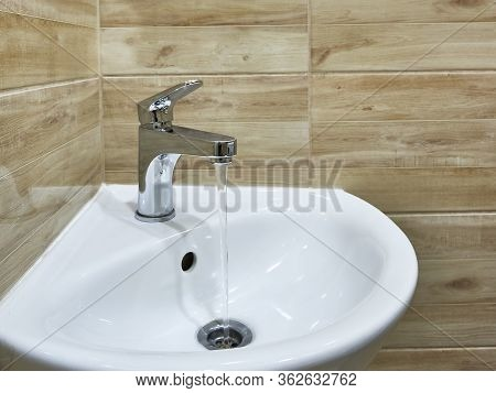 Modern Water Tap In The Bathroom With Running Flowing Water In Sink. Open Chrome Sink Faucet. Modern